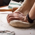 kneading dough to make great pizza