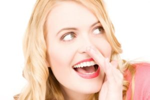 laughing blonde girl with hand over mouth