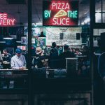pizza shop with neon signs and people sitting in booths